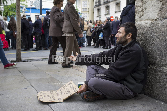 A homeless man begs on a street corner during a religious parade in Granada, Spain. - Philip Wolmuth - 2013-05-18
