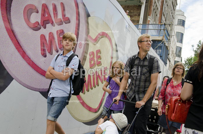 A family walk past a construction site hoarding in Oxford Street, London. - Philip Wolmuth - 2013-08-05