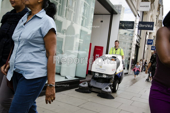 A City of Westminster street cleaner, employed by French multinational private contractor Veolia, sweeps the pavement outside shops in Oxford Street, London. - Philip Wolmuth - 2013-08-05
