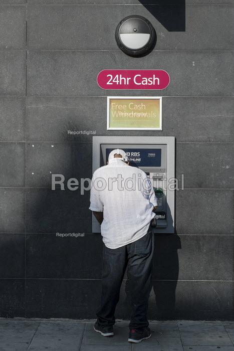 A man makes a withdrawal at an ATM cash machine, Cricklewood, London. - Philip Wolmuth - 2013-08-29