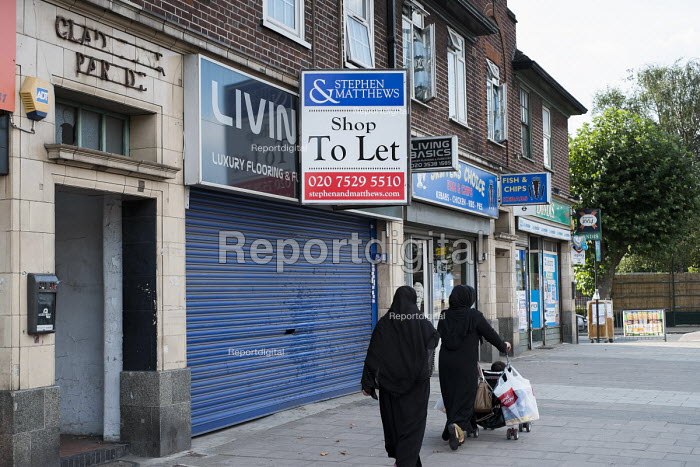 Two women wearing traditional dress pass empty shop premises to let in Cricklewood, London. - Philip Wolmuth - 2013-08-29