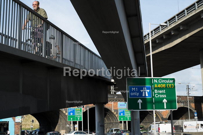 A cyclist on a raised walkway next to the North Circular Road flyover and the slip road to the M1 motorway at Staples Corner, London. - Philip Wolmuth - 2013-08-29
