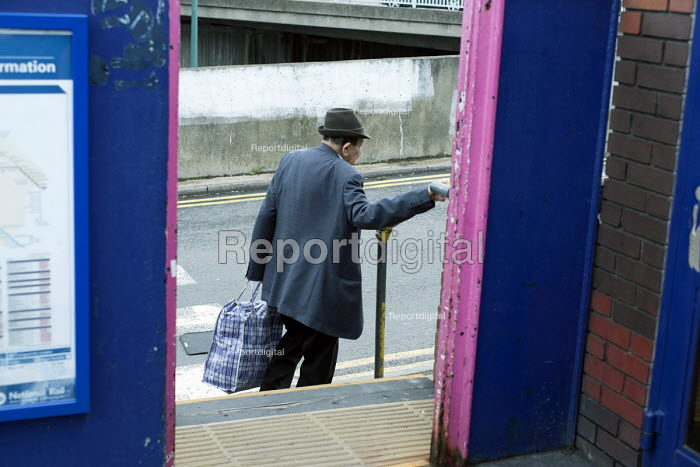 Elderly man carrying a bag uses a handrail on some steps at Hendon railway station, London. - Philip Wolmuth - 2013-09-12