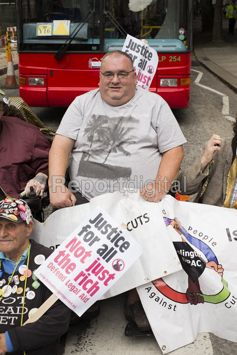 UK Uncut and Disabled People Against the Cuts block the road outside the Royal Courts of Justice in protest at proposed cuts to Legal Aid. - Philip Wolmuth - 2013-10-05