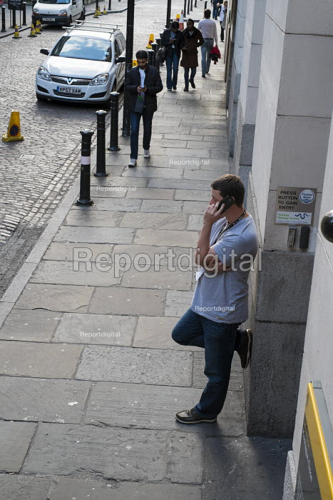 A young man speaks on a mobile phone on a street in Southwark, London. - Philip Wolmuth - 2013-09-20