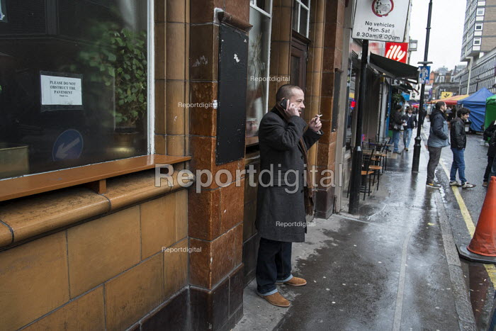 Man smoking and using a mobile phone outside a pub, Soho, London. - Philip Wolmuth - 2014-01-30