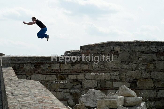 Parkour specialist practices a wall-to-wall leap, Buda Castle, Budapest. - Philip Wolmuth - 2014-06-29