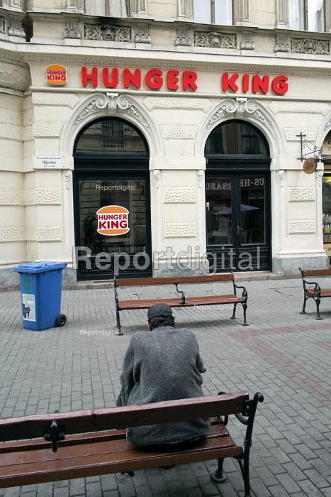 Homeless man on a bench opposite Hunger King, a restaurant modelled on Burger King, Budapest,Hungary - Philip Wolmuth - 2014-06-30