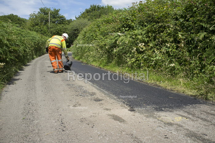 Worker from contractor Lafarge Tarmac sealing a repair on a country road in Hereforshire. - Philip Wolmuth - 2014-07-10
