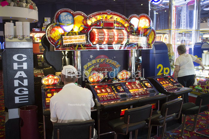 Man at a slot machine on Clacton Pier. The resort is the second most deprived seaside town in the UK. - Philip Wolmuth - 2014-08-20