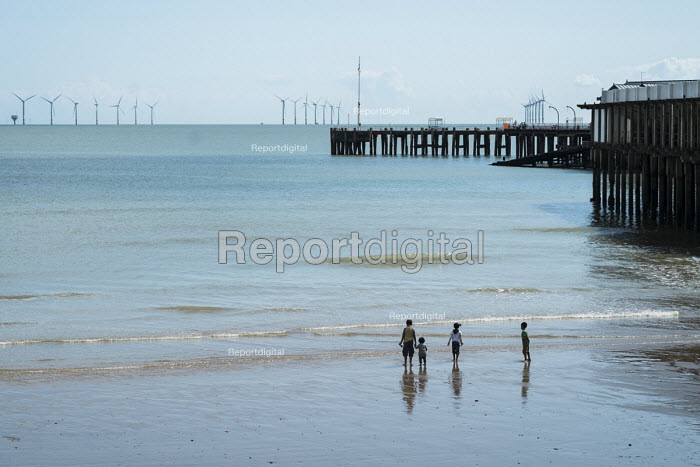 Children play on the beach by Clacton Pier and the London Array offshore wndfarm. The resort is the second most deprived seaside town in the UK. - Philip Wolmuth - 2014-08-20