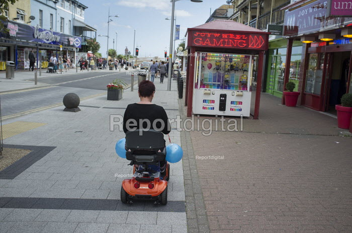 Woman on a mobility scooter in Clacton. The resort is the second most deprived seaside town in the UK. - Philip Wolmuth - 2014-08-20