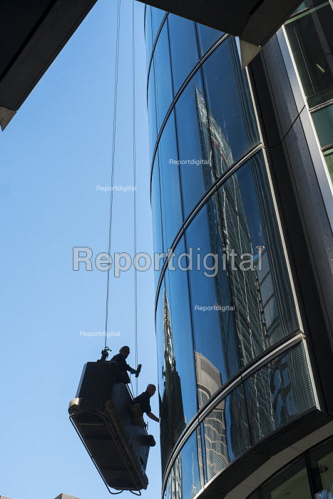Window cleaners working from a cradle on a high-rise office block in the City of London close to 30 St. Mary Axe (The Gherkin). - Philip Wolmuth - 2015-02-17