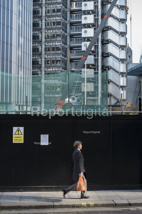 A City of London worker walks past a construction site next to the Lloyds Building. - Philip Wolmuth - 2015-02-17