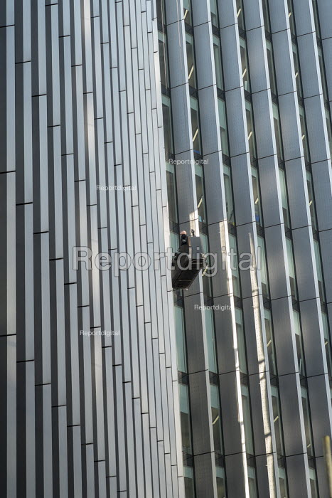 A maintenance worker inspecting windows from a cradle on a high-rise office block in the City of London. - Philip Wolmuth - 2015-02-17