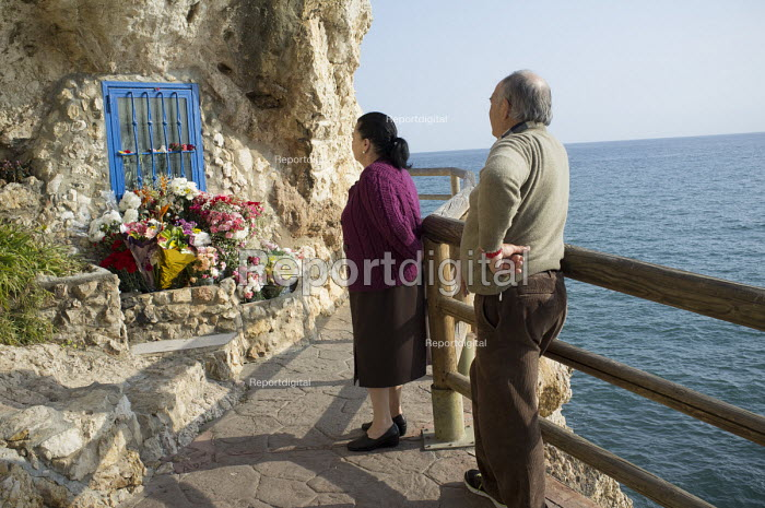 An elderly couple pay respects at a seaside shrine, La Cala del Moral, Malaga, Spain. - Philip Wolmuth - 2015-03-15