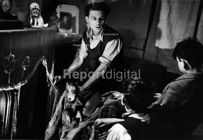 Working class family in their London home with a domesticated pet monkey in 1952. The monkey appears to be drinking milk or water from a glass. .... - Elizabeth Chat - 1952-07-11