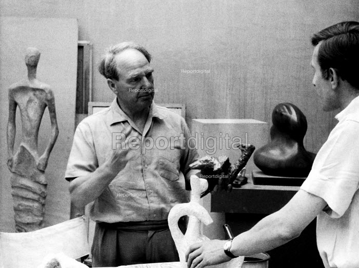 Sculptor, Henry Moore, giving instructions to his assistant at his studio in Much Hadham, Hertfordshire in the early to mid 1950s. .... - Felix H. Man - 1953-05-11