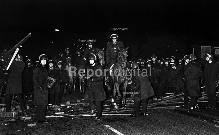 Riot police remove a barricade set up by striking miners (out of picture) in South Elmsall village after attempts earlier in the day to get one scab miner through an NUM picket line and into work at Frickley Pit during the year long miners' strike - John Harris - 1984-11-15