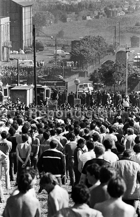 MIners trying to picket look on as lorries in the distance behind poilce lines transport coke from the Orgreave coking plant during the miners strike - John Harris - 1984-06-18