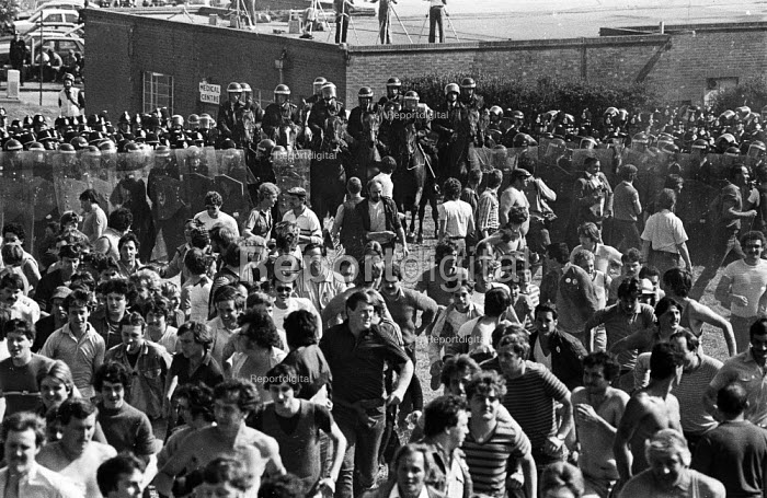 Miners start to run as police lines open and riot police officers on horseback advance towards the mass picket lines at the Orgreave coking plant during the miners strike - John Harris - 1984-06-18