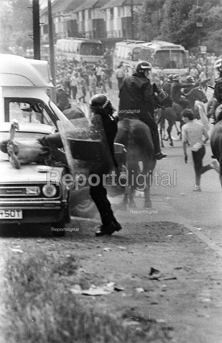 Battle of Orgreave. Bare-chested miners holds up his hand to try and protect himself from advancing riot police officer with baton drawn during violent clashes between miners and riot police officers on the picket lines at the Orgreave coking plant during the miners strike - John Harris - 1984-06-18