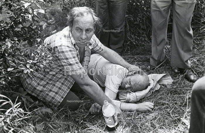 Older miner is cared for by a friend after being injured on the picket line during violent clashes between miners and riot police officers on the picket lines at the Orgreave coking plant during the miners strike - John Harris - 1984-06-18