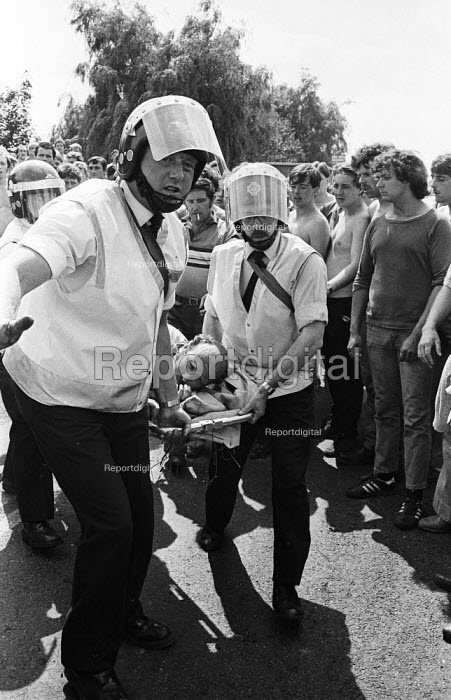 Older miner is carried away by ambulance staff, after he was injured on the picket line during violent clashes between miners and riot police officers on the picket lines at the Orgreave coking plant during the miners strike. - John Harris - 1984-06-18