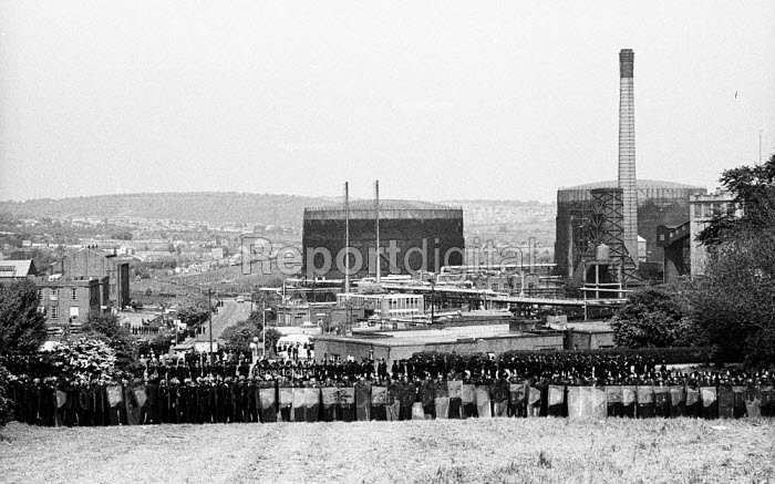 Ranked lines of police officers and riot police officers prevent striking miners from approaching the Orgreave coking plant to picket during the miners' strike - John Harris - 1984-05-28