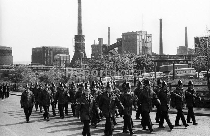Uniformed police officers march into position during a mass picket of the Orgreave coking plant during the miners strike - John Harris - 1984-05-28