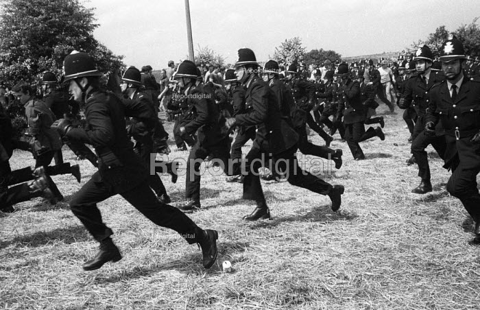 Uniformed police police officers running at full pelt during a mass picket ofthe Orgreave coking plant during the miners strike Photographer Martin Shakeshaft is the first figure on the left of the photograph - John Harris - 1984-05-29