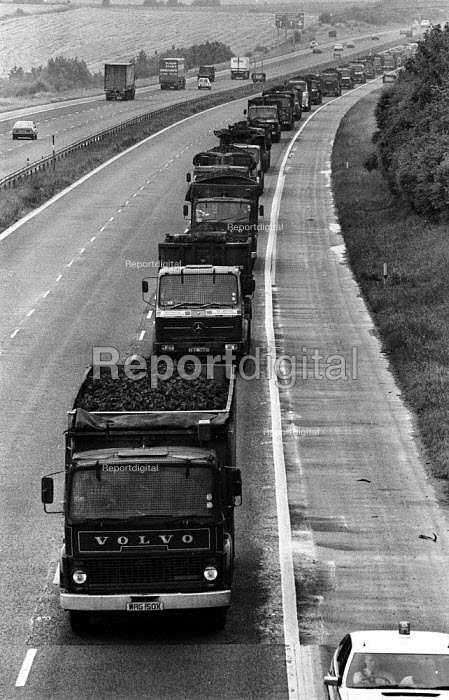 Lorries fitted with grilles and escorted by police vehicles in a convoy carry coal along the motorway from Llanwern to Port Talbot steelworks during the Miners Strike, South Wales - John Harris - 1984-08-01