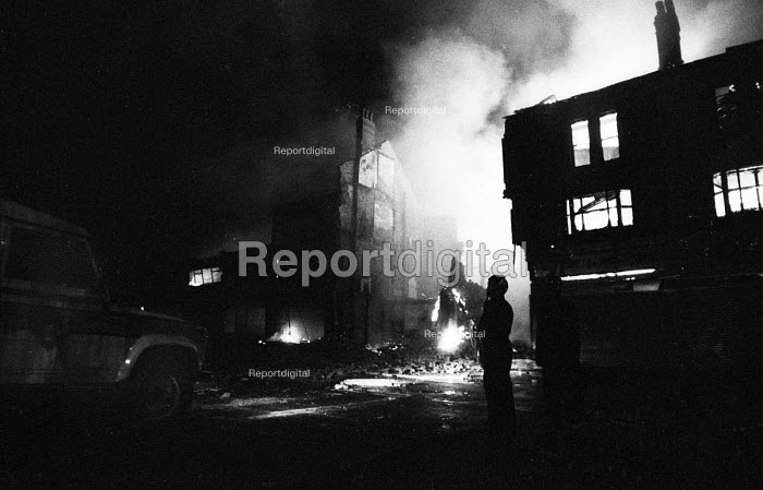Riot police on the streets of Handsworth as fires set off during the riots burn in the buildings behind, Birmingham. - John Harris - 1985-09-10