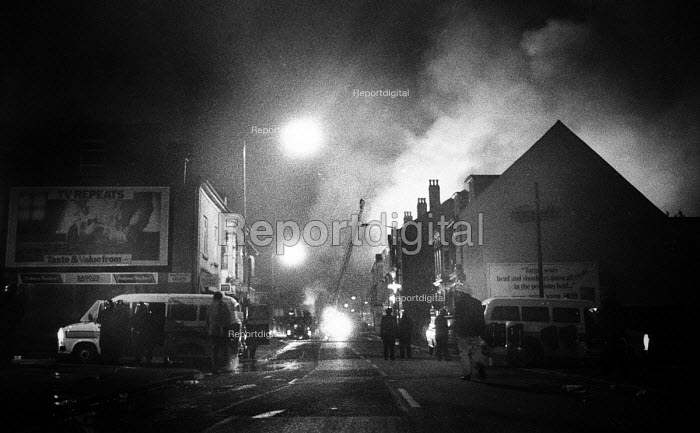 Riot police on the streets of Handsworth as fires set off during the riots burn in the buildings behind them attended by fire crews - John Harris - 1985-09-10