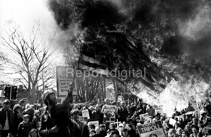 Burning the American Flag. Bombing of Libya. Upper Heyford Air Base Campaigners protest against the use of US air bases on British soil used by American F111s to bomb Libya. A man burns the American flag, the Stars and Stripes, in anger. 20th Tactical Fighter Wing, RAF Upper Heyford Air Base - John Harris - 1986-04-20