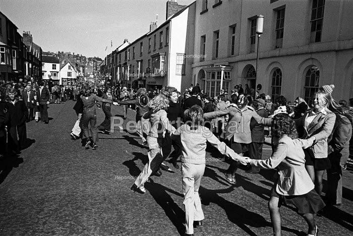 Durham Miners Gala, 1974. Following tradition, children from the pit villages dance in the street in front of their Lodge banner as it is paraded in the annual Big Meeting. - John Sturrock - 1974-07-14
