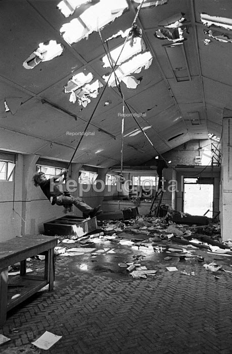 Children playing in a disused youth club, Splott, Cardiff 1975. Swinging on a roop swing. - John Sturrock - 1975-06-21