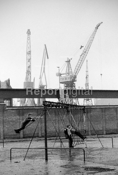 Children playing on the swings in a playground with the cranes of the Govan shipyard towering behind them, Glasgow 1976 - John Sturrock - 1976-04-27