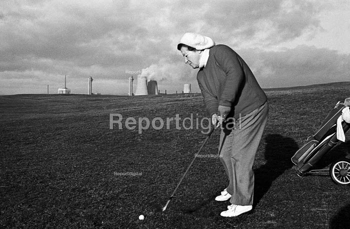 Female golfer playing a shot with the chimneys of Windscale nuclear power plant in the near distance behind her, 1977, Seascale Golf Course, Cumbria. - Mike Khan - 1977-01-10