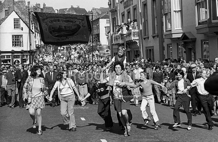 Durham Miners Gala, 1974. Following tradition, families and children from the pit villages dance in the street in front of their Lodge banner as it is paraded in the annual Big Meeting. - Angela Phillips - 1974-07-14