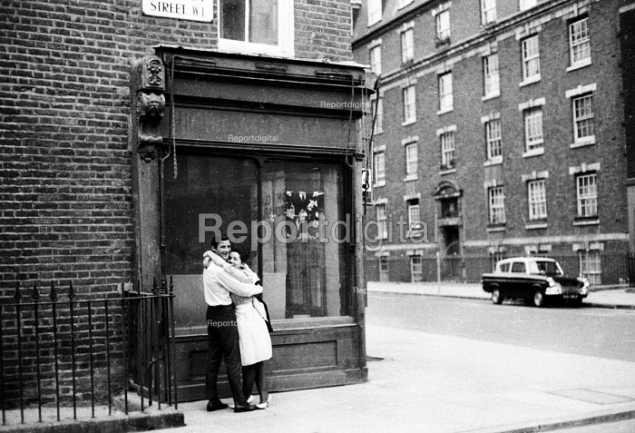 Young couple hugging on a street, West End in the early 1960's London - Romano Cagnoni - 1962-05-11
