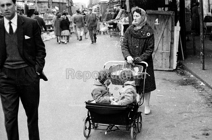 Woman, looking slightly downcast, with two children in a buggy in a London street market in the early 1960's.