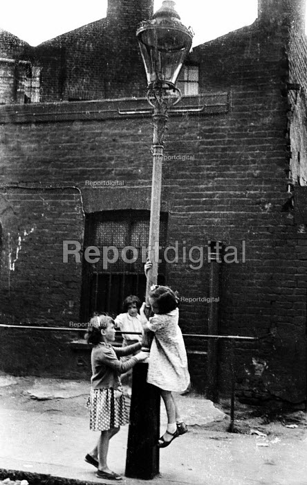 Young girls playing in the street outside their homes in a run-down part of London, probably near King's Cross, in the early 1960's. London - Romano Cagnoni - 1962-07-11