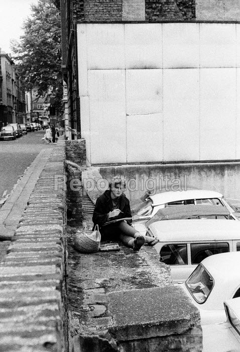 Woman writing or drawing beside a car park in London in the early 1960's. - Romano Cagnoni - 1962-07-11