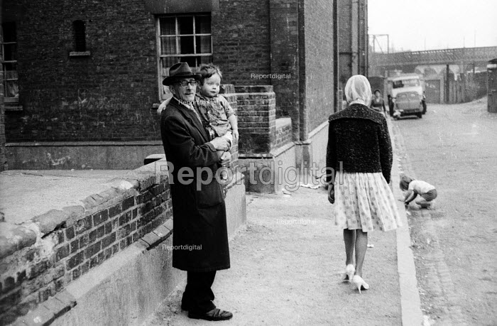 London street scene, probably near to King's Cross, in the early 1960's. Older man carrying young boy. .... - Romano Cagnoni - 1962-07-11