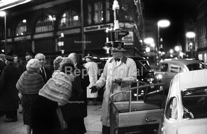 Uniformed hotel doorman wearing a top hat opens car door for fur clad guest. West End, London early 1960's - Romano Cagnoni - 1962-07-11