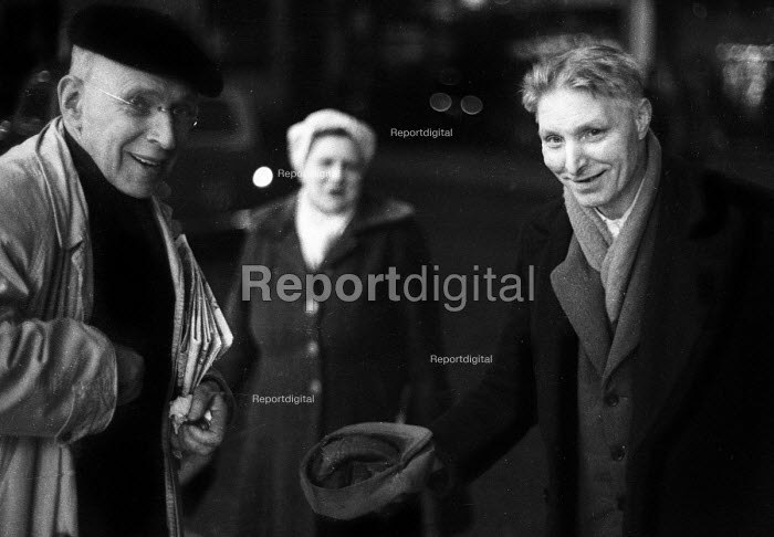 Simon Guttmann, with beret, preparing to give money to a busker, with cap in hand, in the West End of London in the early 1960's - Romano Cagnoni - 1962-07-11