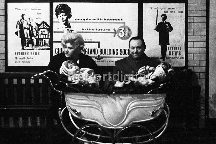 Couple in the early 1960's with three young children in a pram waiting at an underground station for a tube train to arrive, with advertisements for housing and jobs small ads in the Evening News behind them. London - Romano Cagnoni - 1962-07-11