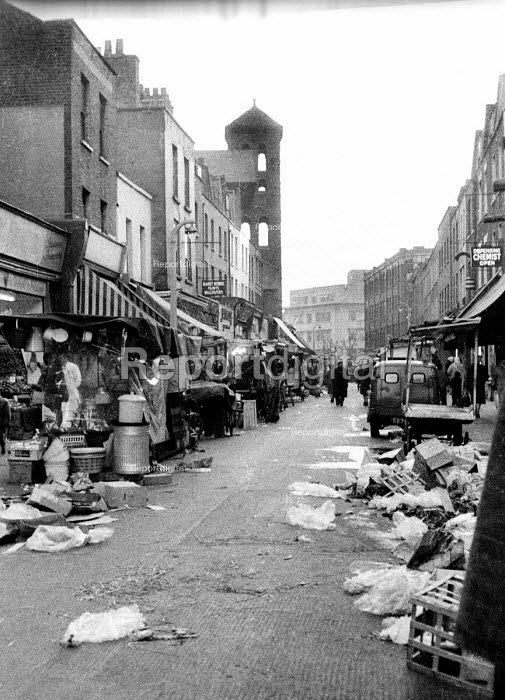 Exmouth Market street market in the then borough of Finsbury, now Islington, in the early 1960's. On the left is tower of the Holy Redeemer Church and in the distance Mount Pleasant Sorting Office. .... - Romano Cagnoni - 1964-07-11