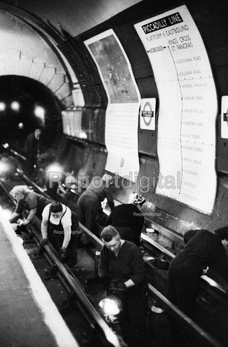 Fluffers in the early 1960's - workers, usually women, who clean the dust and dirt from the tracks on the underground in the early hours of the morning when the tube network is closed down. Here, the fluffers can be seen between the tracks at King's Cross Station on the Piccadilly Line. .... - Romano Cagnoni - 1964-07-11